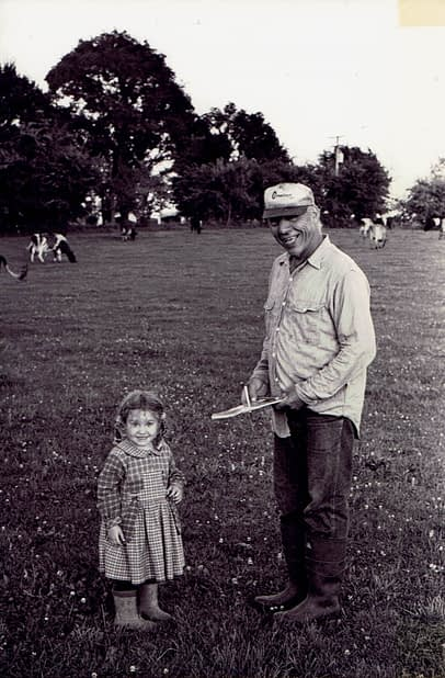 A little girl and her father in cow pasture